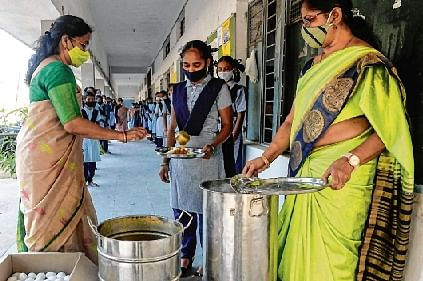 Teachers serve mid-day meal to students during a lunch break after the schools for classes IX and X reopen in Hyderabad.