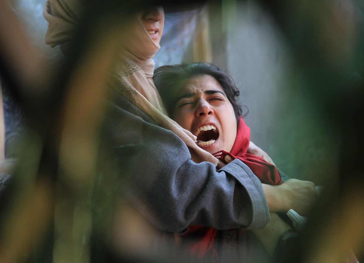 A girl mourns outside the damaged house in which Militants took shelter during an encounter between Militants and security forces in at a Village in Budgam district of Kashmir.