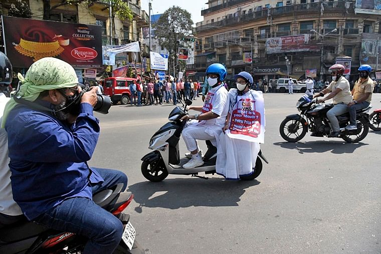 West Bengal Chief Minister Mamata Banerjee along with Mayor of Kolkata and Minister in Charge - Urban Development and Municipal Affairs Government of West Bengal Firhad Hakim protesting on the streets of Kolkata. Hakim rides the scooter while the CM sat behind sporting a slogan against the fuel price