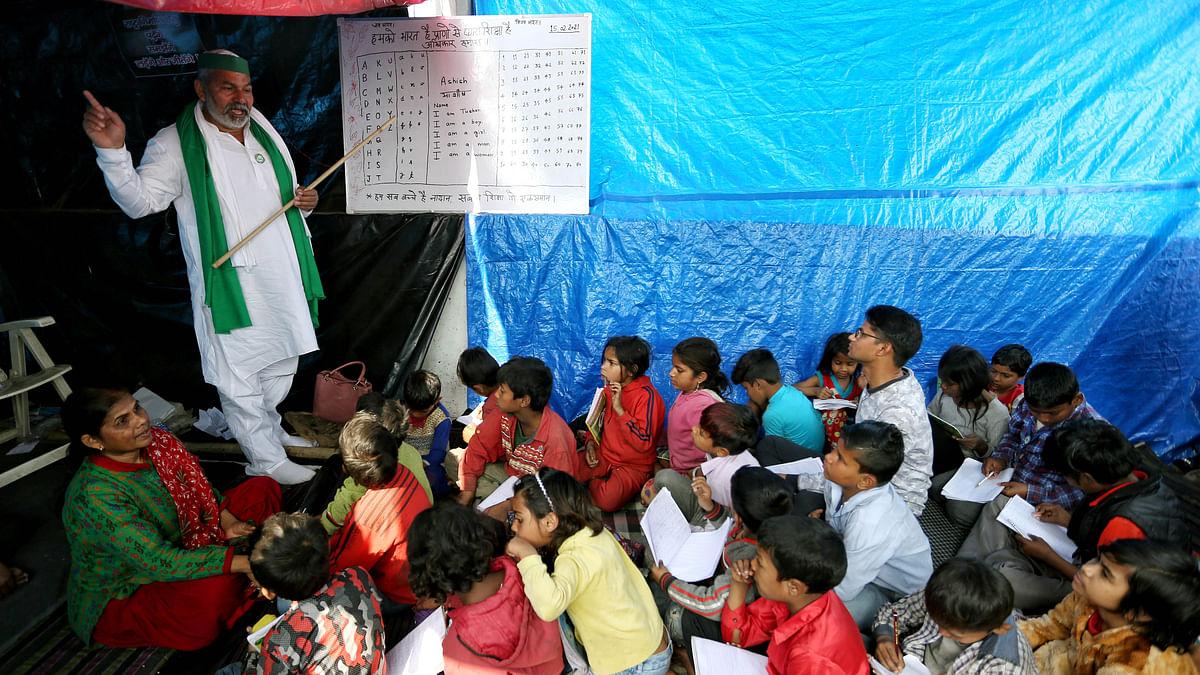Farmer leader Rakesh Tikait teaches children at makeshift school at protest site