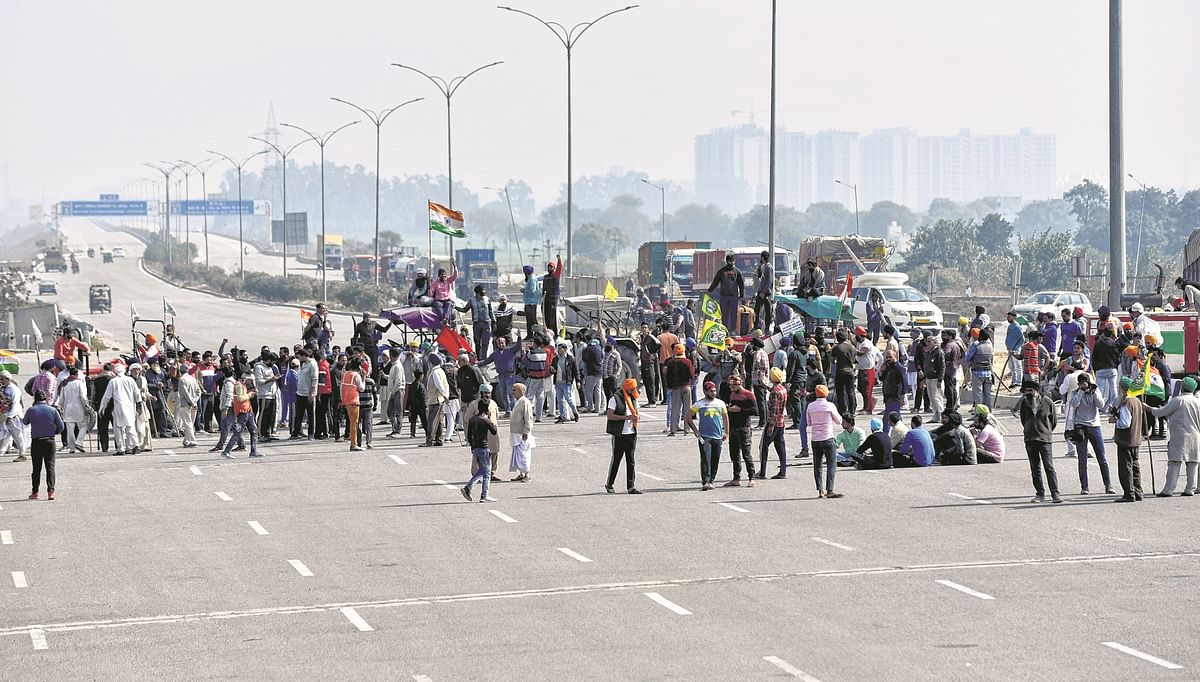 Farmers block Kundli Manesar Palwal Expressway (KMP) near Singhu border during their country-wide 'Chakka Jaam' against farm laws, in Delhi on Saturday.
