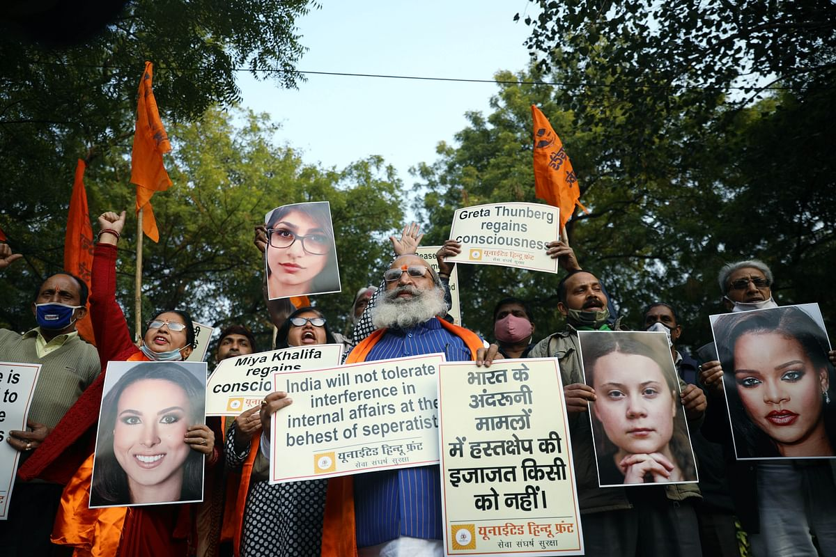 Members of United Hindu Front hold placards of international celebrities who lent their support to farmers protest, in New Delhi on Thursday.