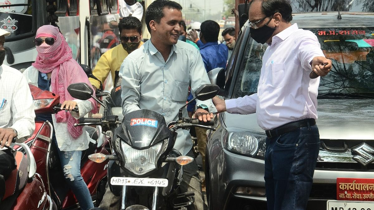 An official intercepts a person driving a motorbike bearing a sticker of 'police', in Ujjain on Friday. After seizing the keys of bike, the person was sent to the make-shift jail for the violation of Covid-19 protocol.