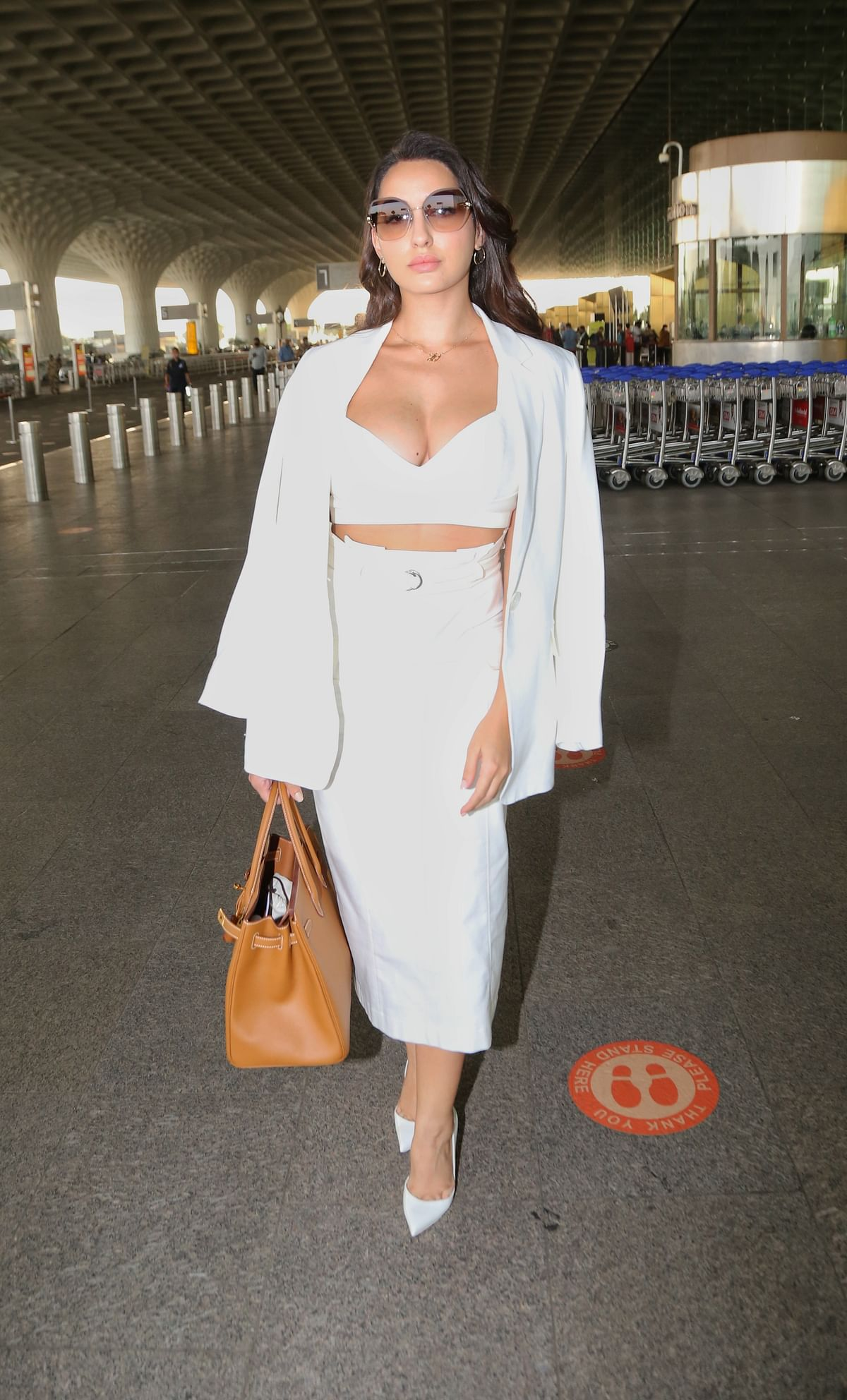 Nora Fatehi turns heads at Mumbai airport in a white ensemble with a plunging neckline