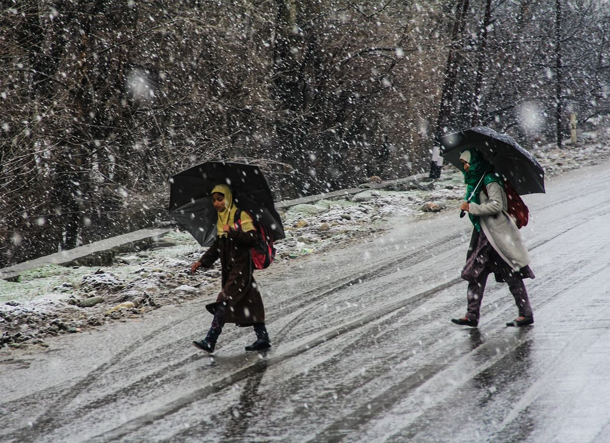 Young girls walk with umbrellas during fresh snowfall in part of Kashmir.