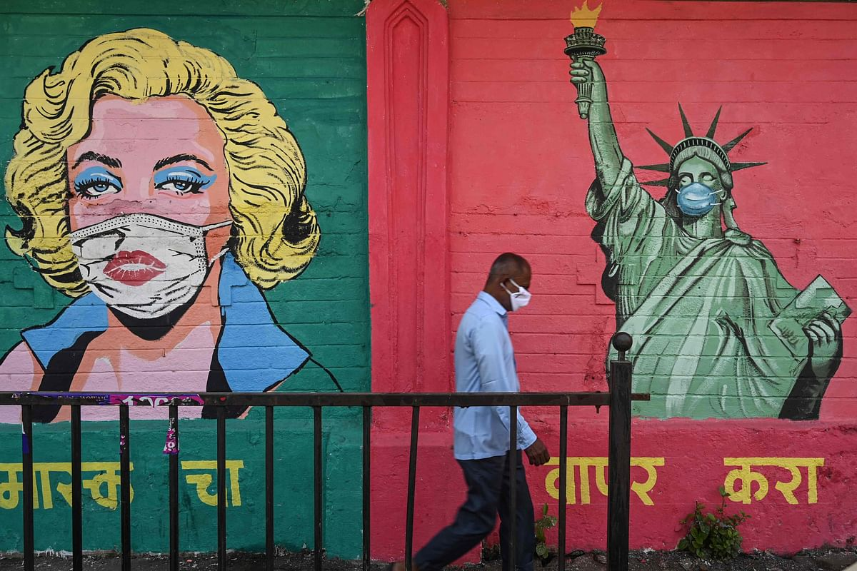 """A pedestrian walks past a mural of Hollywood actress Marilyn Monroe (L) and the """"Statue of Liberty"""", wearing facemasks to spread awareness about the COVID-19 coronavirus, in Mumbai on March 31, 2021"""