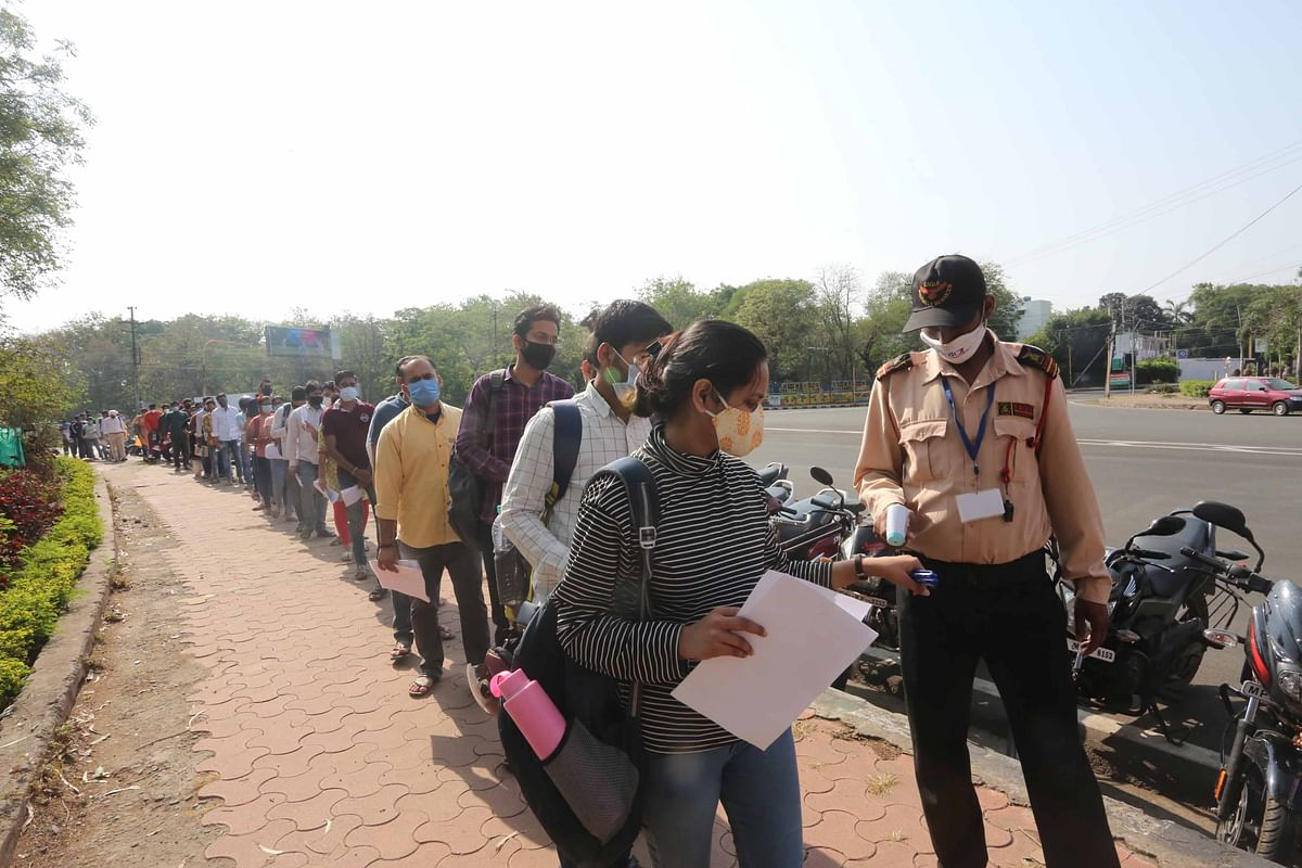 MPPSC candidates undergo thermal screening before entering the examination hall at the Subhash School in Bhopal on Sunday.