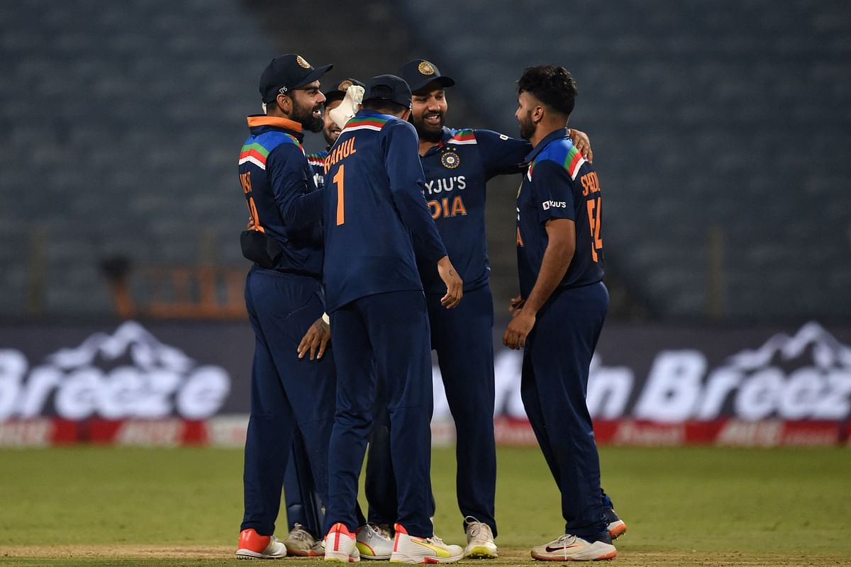 India captain Virat Kohli (L) celebrates with teammates after taking the catch of Englands Adil Rashid (not pictured) during the third and final one-day international (ODI) cricket match between India and England at the Maharashtra Cricket Association Stadium in Pune on March 28, 2021.