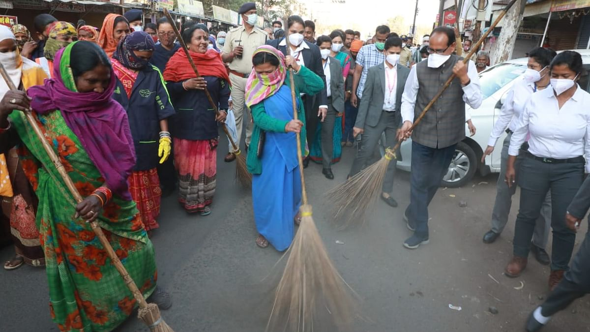 Chief Minister Shivraj Singh Chouhan along with women sanitation workers participate in a cleanliness drive on International Womens Day, in Bhopal on Monday.