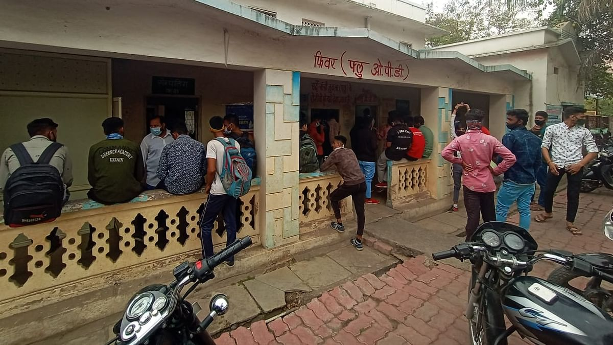 Youngsters wait outside a government fever clinic for corona test, in Ujjain on Thursday