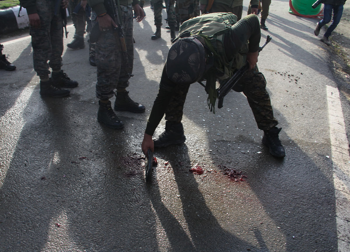 CRPF personnel cleanes the blood stains after suspected militants attack on security forces at Lawaypora on the outskirts of Srinagar.