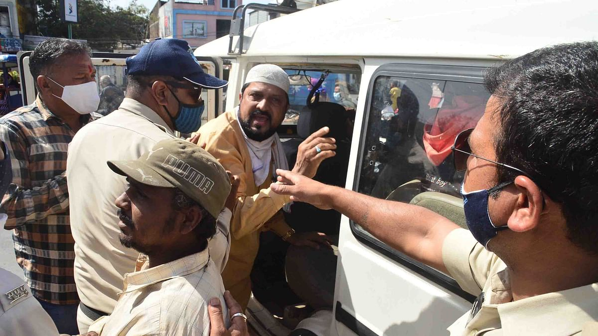 Policemen directs a person to board government vehicle; over 210 such violators were sent to the temporary jail in Ujjain on Friday