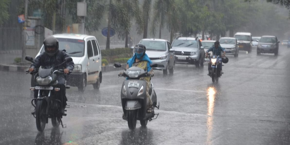 Commuters brave the early morning rain in Bhopal on Friday.