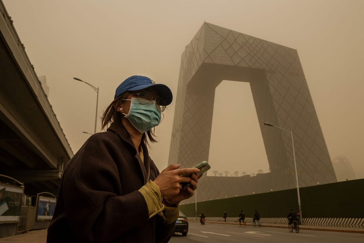 A woman waits at a bus stop during a sandstorm in the financial district in Beijing on March 15, 2021.