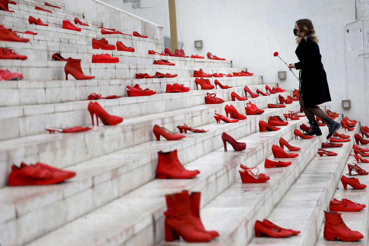 A woman puts a red flower at an installation of womens red shoes displayed on staircase, as a symbol to denounce violence against women, at Durresi main square in Tirana, on International Womens Day, on March 8, 2021.