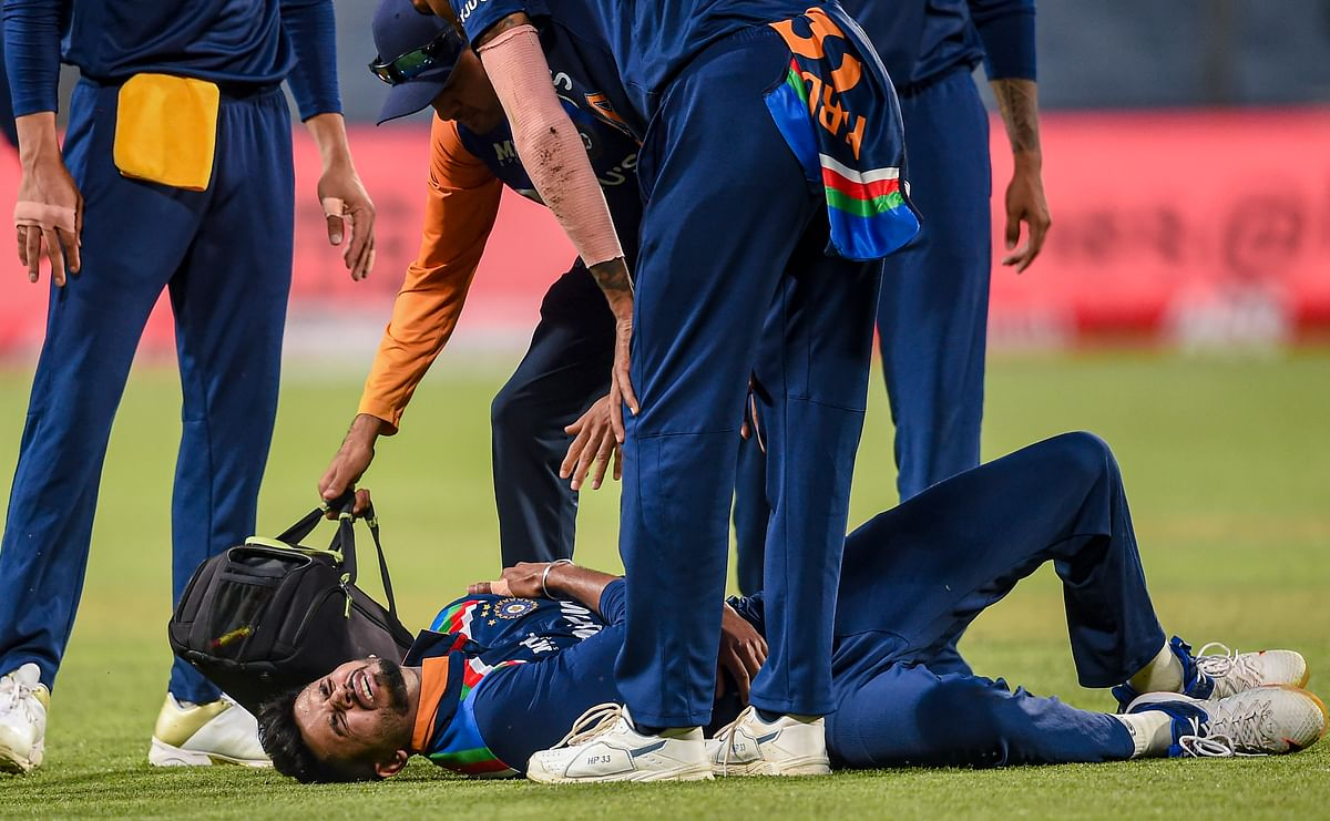 Indian cricketer Shreyas Iyer being attended by teammates after he injured himself during the first One Day International cricket match against England at Maharashtra Cricket Association Stadium, in Pune, on Tuesday