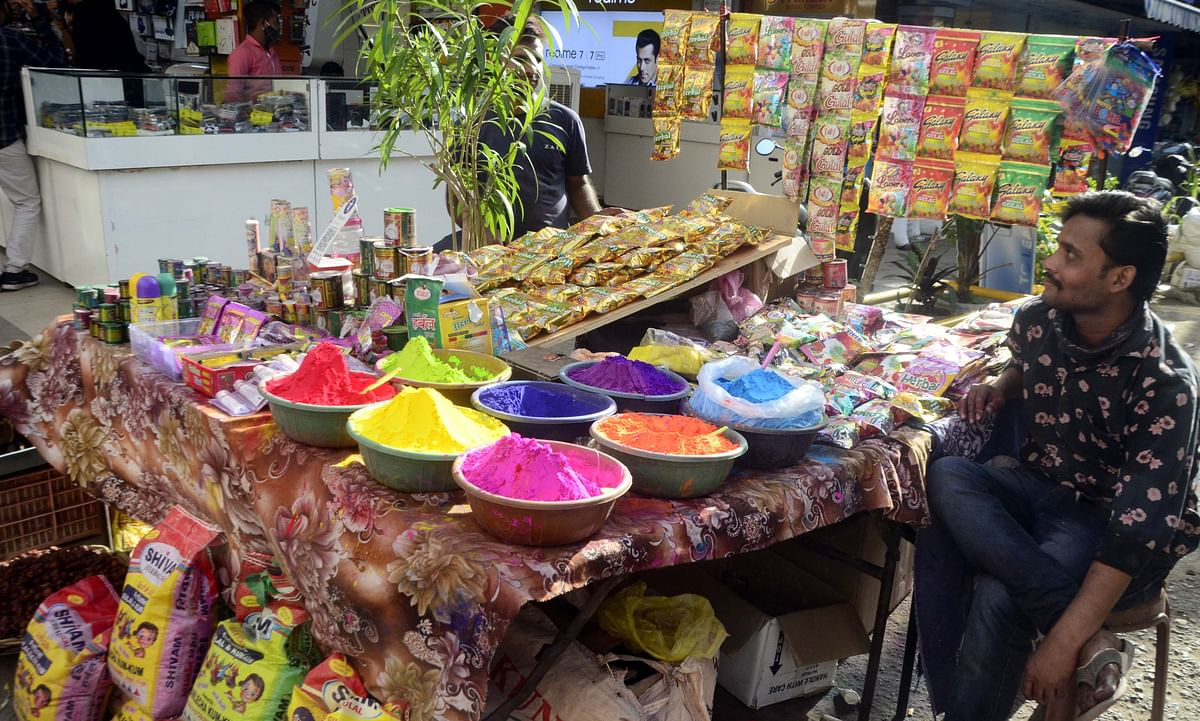 A vendor selling colours waits for customers in New Market ahead of Holi.