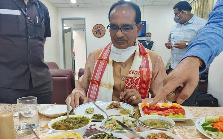 Chief minister Shivraj Singh Chouhan relishing local delicacies in Assam on Monday