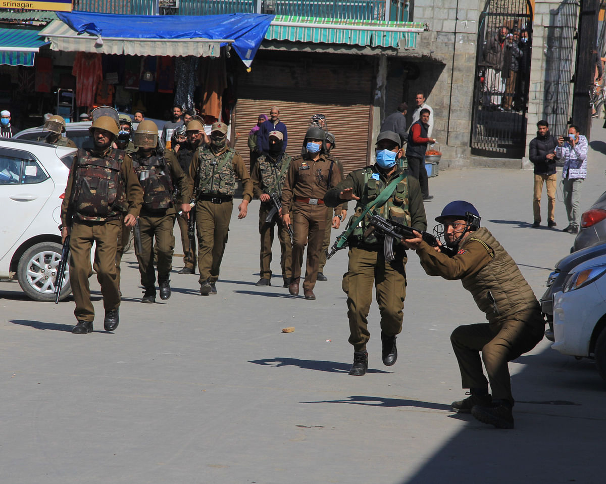 Police officer aims his pellet gun towards Protesters during a protest after Friday prayers in Srinagar March 5, 2021 to demand the release of Mirwaiz Umar Farooq, Kashmir's Chief cleric who has been under house arrest for 20 months.