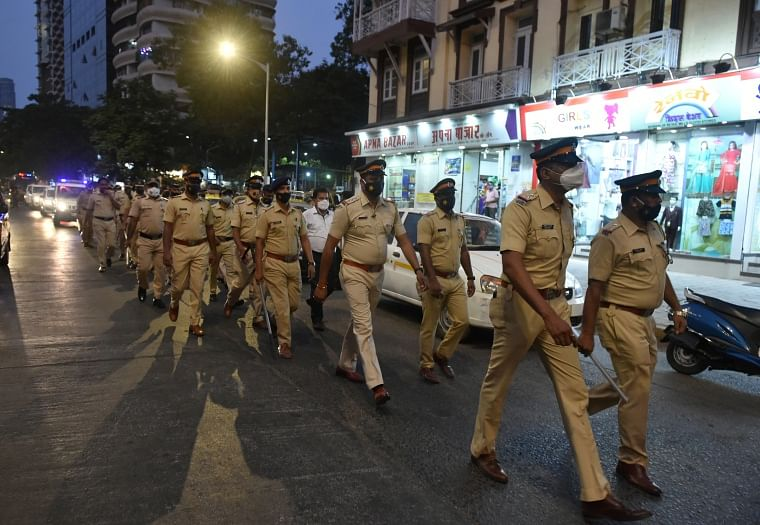 Police personnel conduct a flag march during night curfew, imposed by the authorities to curb the spread of coronavirus, in Mumbai