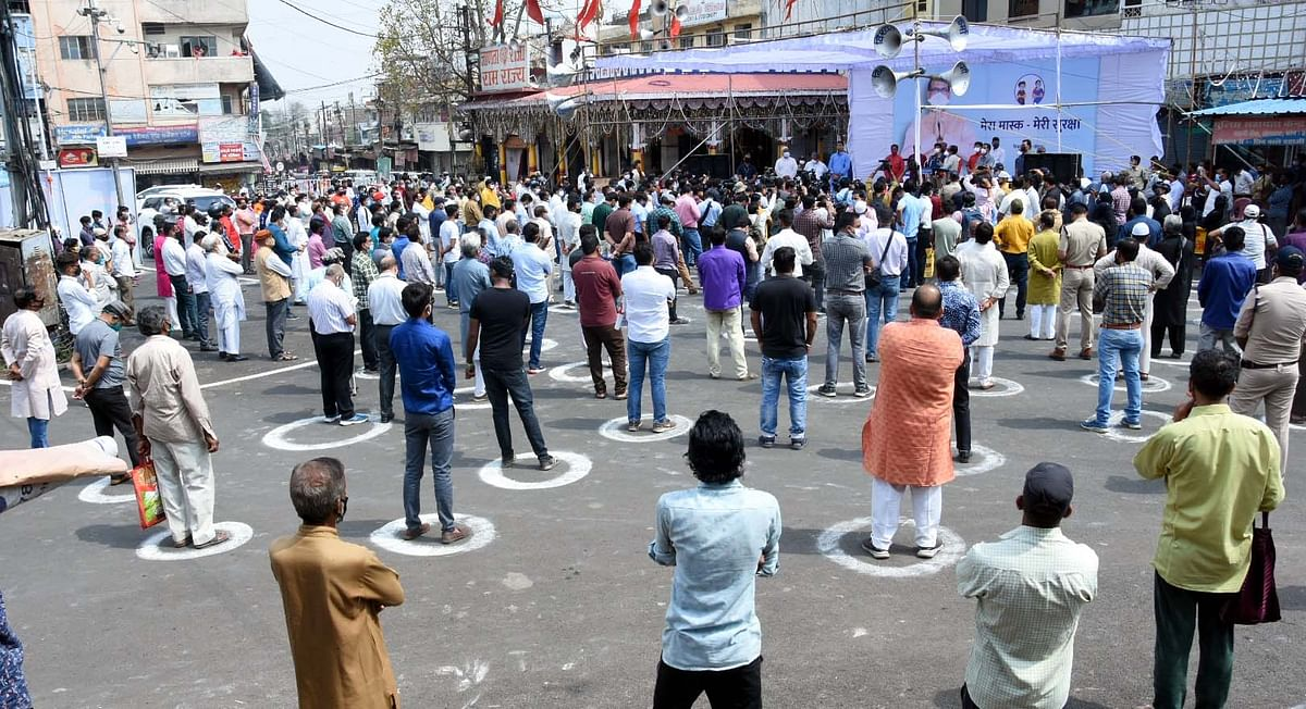 People stand on the road to observe two-minute silence as a state-wide campaign My Mask My Security launched by the State Chief Minister Shivraj Singh Chouhan to maintain COVID-19 safety norms, in Bhopal on Tuesday.