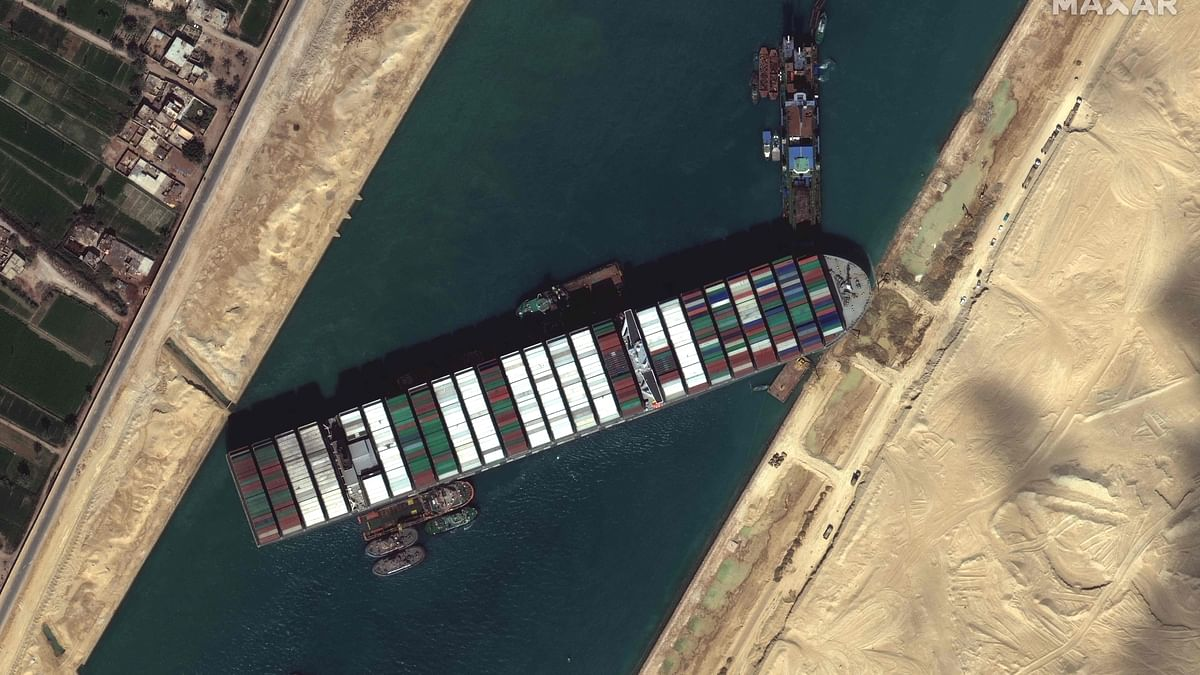 This satellite imagery released by Maxar Technologies shows tug boats and dredgers on March 27, 2021, attempting to free the Taiwan-owned MV Ever Given lodged sideways and impeding all traffic across Egypts Suez Canal.