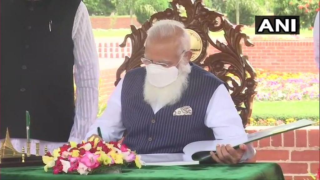 Bangladesh: Prime Minister Narendra Modi signs the visitors' book at National Martyrs' Memorial in Dhaka.