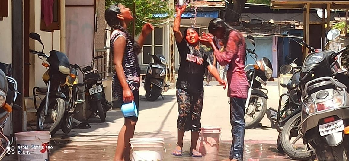 Three friends get wet during Holi play in Ujjain