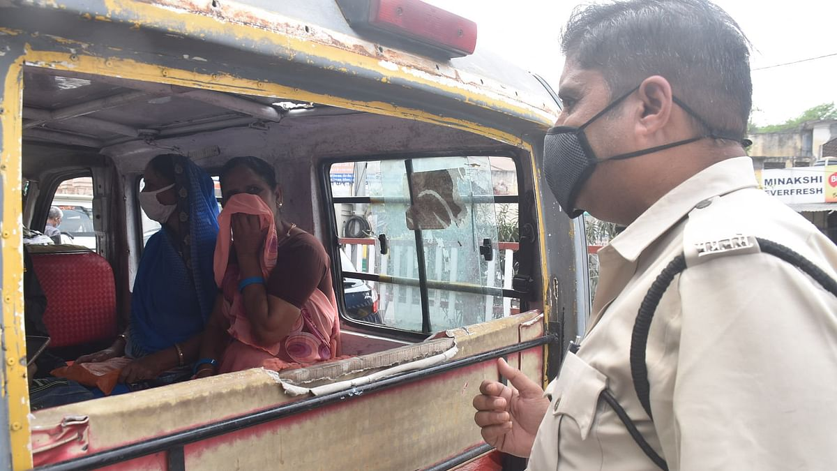A policeman cautions a women passengers to follow the Covid-19 protocol, in Ujjain on Thursday``