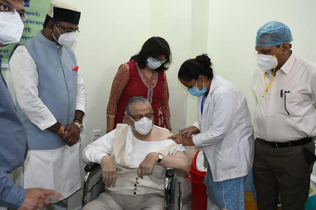 Dr NP Mishra receives vaccine as state medical education minister Vishvas Sarang stands by at Gandhi Medical College in Bhopal on Monday