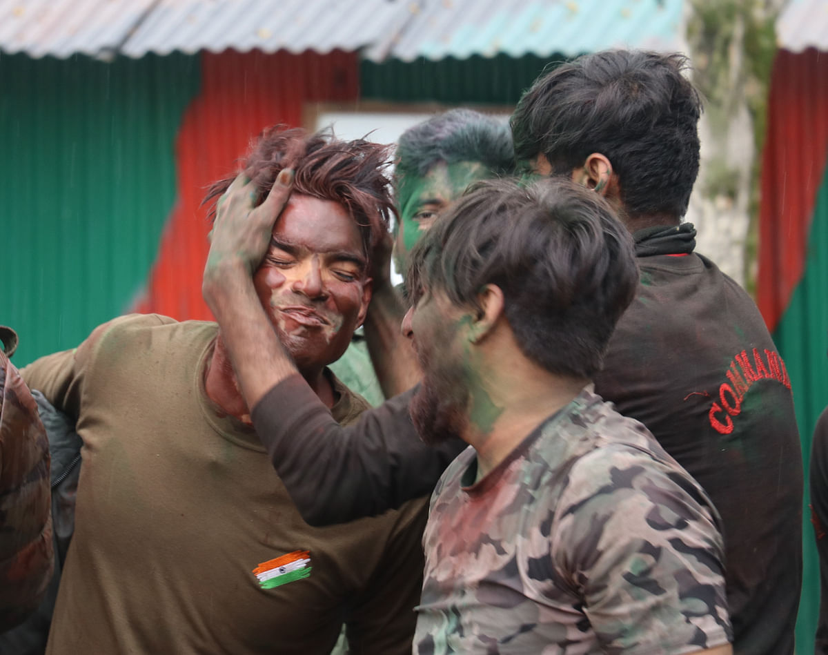 Indian Army soldiers celebrate Holi inside their base camp on the outskirts of Srinagar on March 29, 2021, in Kashmir.