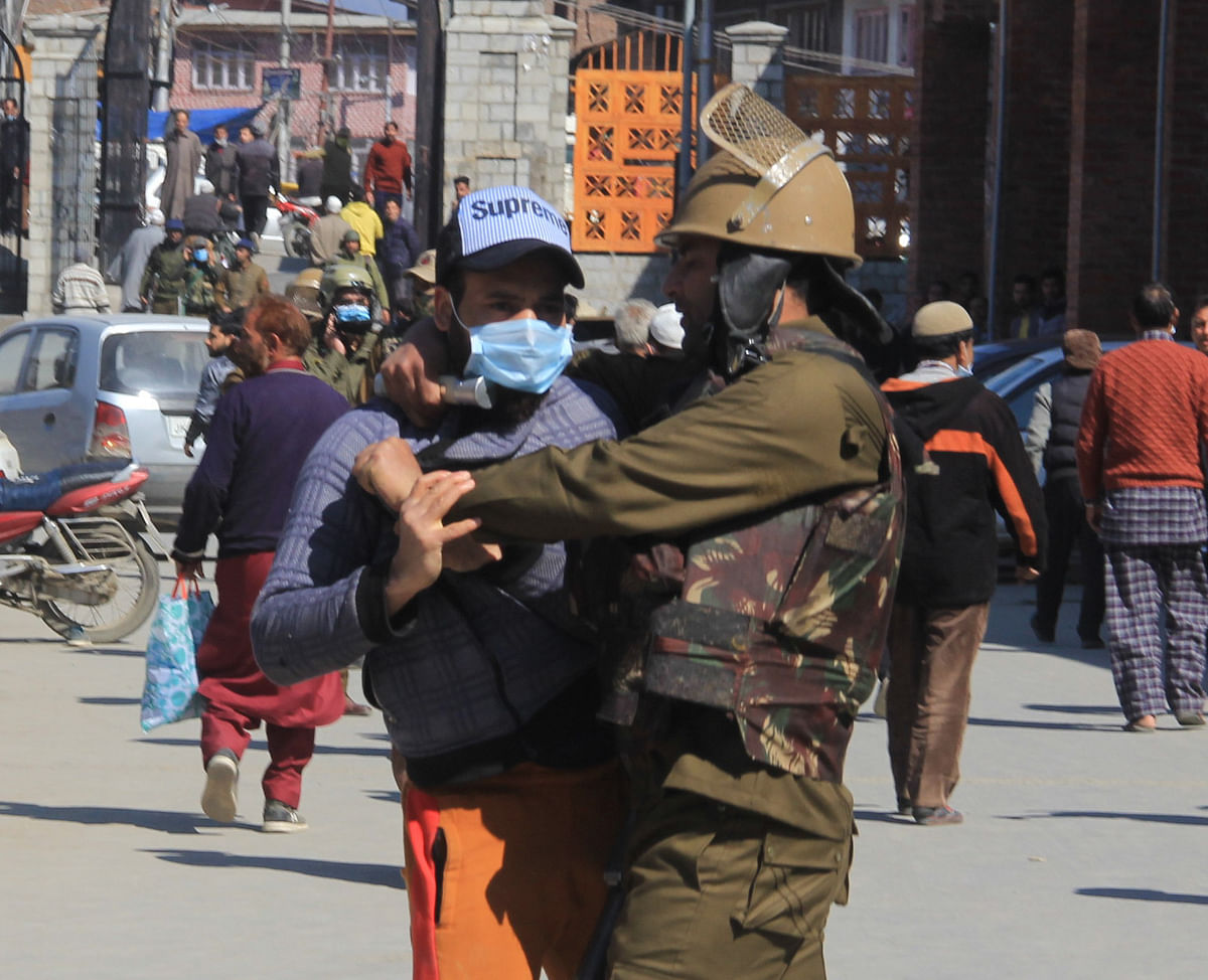 Police man detains a protester during a protest after Friday prayers in Srinagar March 5, 2021 to demand the release of Mirwaiz Umar Farooq, Kashmir's Chief cleric who has been under house arrest for 20 months.