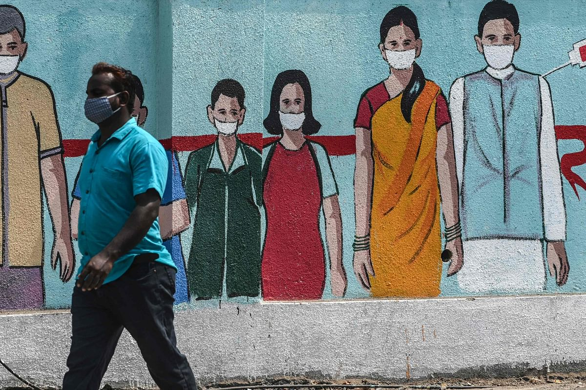 A pedestrian walks past a wall mural depicting medical staff as frontline Covid-19 coronavirus warriors, amidst rising Covid-19 coronavirus cases, in Mumbai on March 29, 2021.