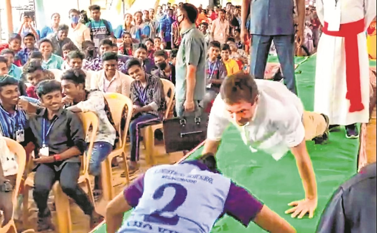 Congress leader Rahul Gandhi does push-ups with a school student obliging her challenge, at Mulagumoodu, Tamil Nadu.