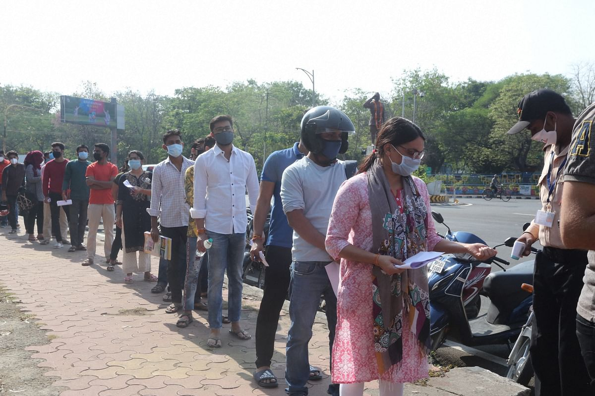Aspirants undergo thermal screening as a precaution against Covid-19, as they arrive to appear for the MPPSC (Mains) exams, in Bhopal on Sunday