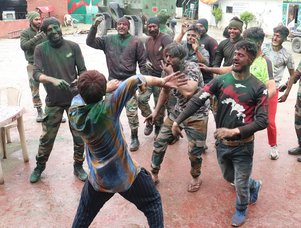 Indian army troopers, smeared in colour, dance during Holi celebrations at their camp on the outskirts of Srinagar, Kashmir.