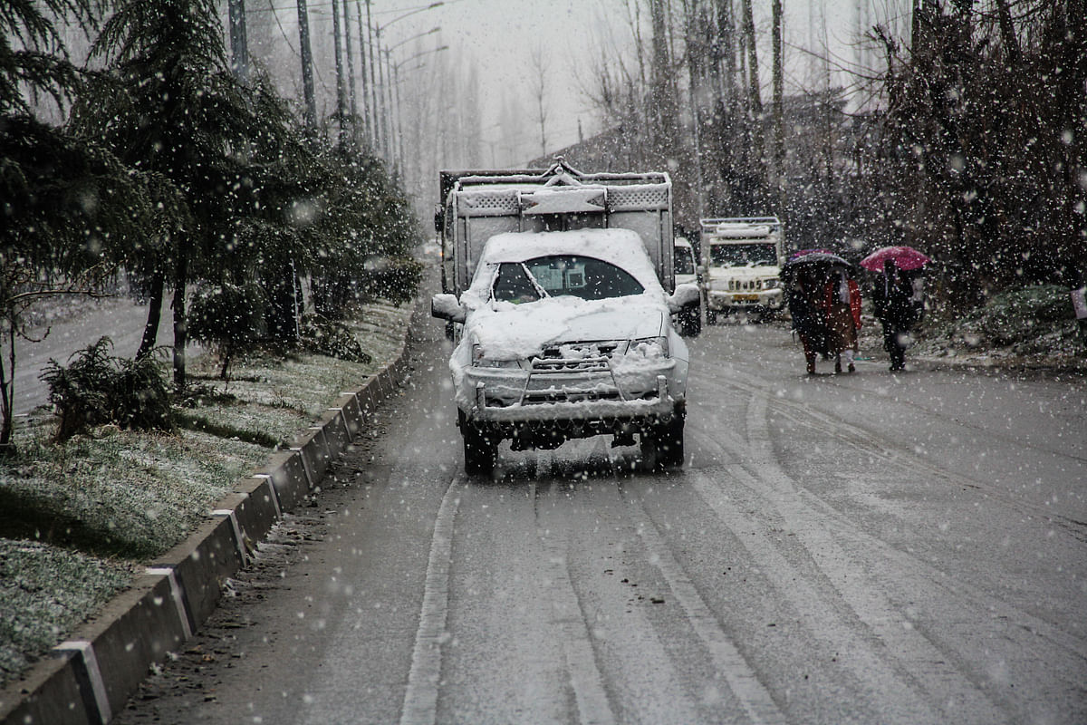 Vehicles moves along a road amid snowfall on March 08, 2021 in parts of Kashmir