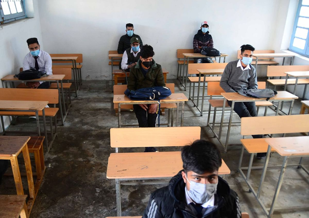 Students wearing face masks as a precaution against the coronavirus, attend classes as Schools reopen after being closed for months due to the COVID-19 pandemic in Srinagar, Kashmir.