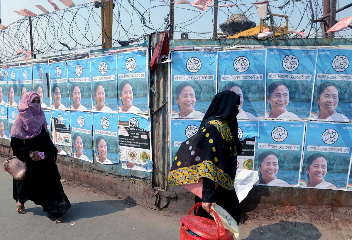 "West Bengal, Mar 06 (ANI): Women walk past the posters of CM Mamata Banerjee depicting the TMCs new election cry, ""Bangla Nijer Mae Ke Chayy"", meaning Bengal wants her own daughter, is seen at Dharmatala, just a day after the deceleration of the candidates for the upcoming West Bengal Assembly Elections, in Kolkata on Saturday."