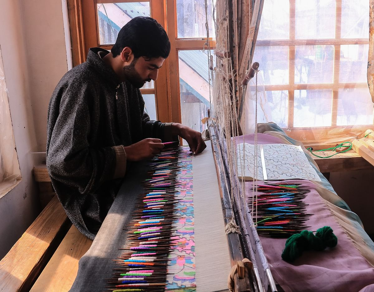 Kashmiri artisan works at the loom to make a Kani Shawl at a village in Budgam district, in the west of Srinagar city.