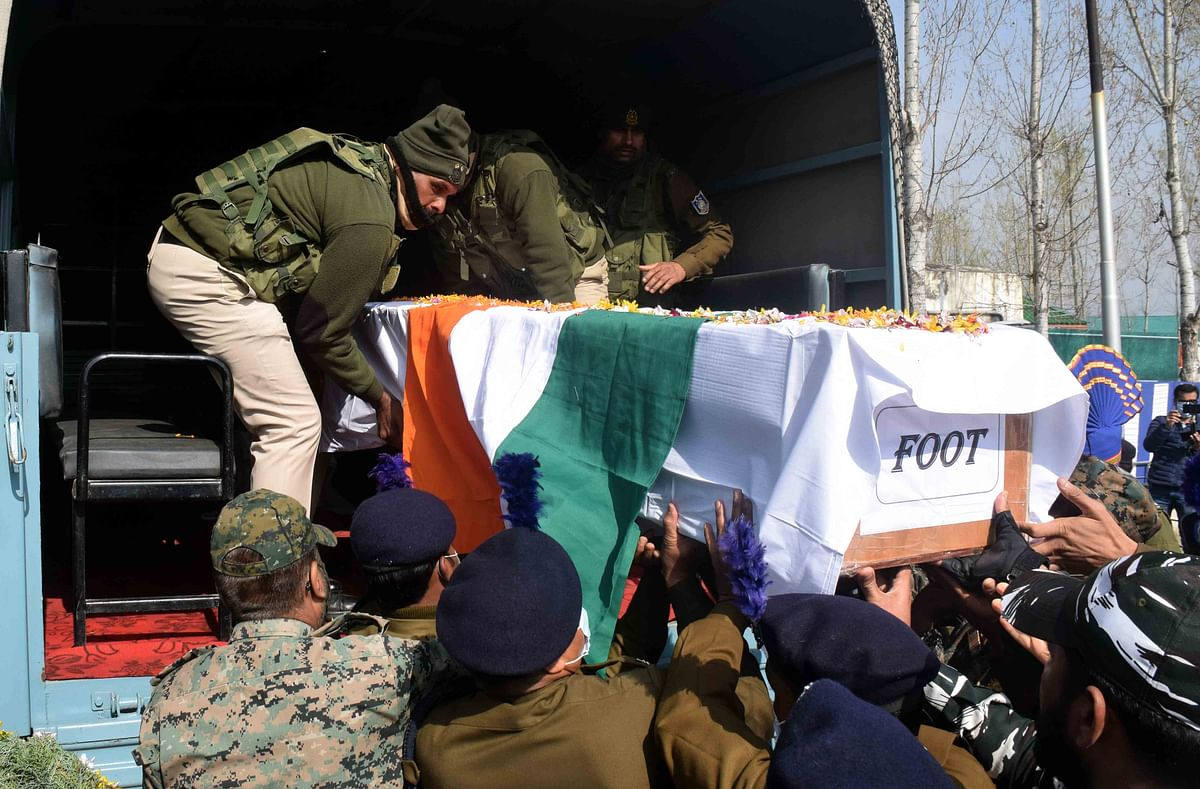 CRPF and police officers are getting coffins of slain CRPF men into a vehicle on Friday, March 26, 2021.
