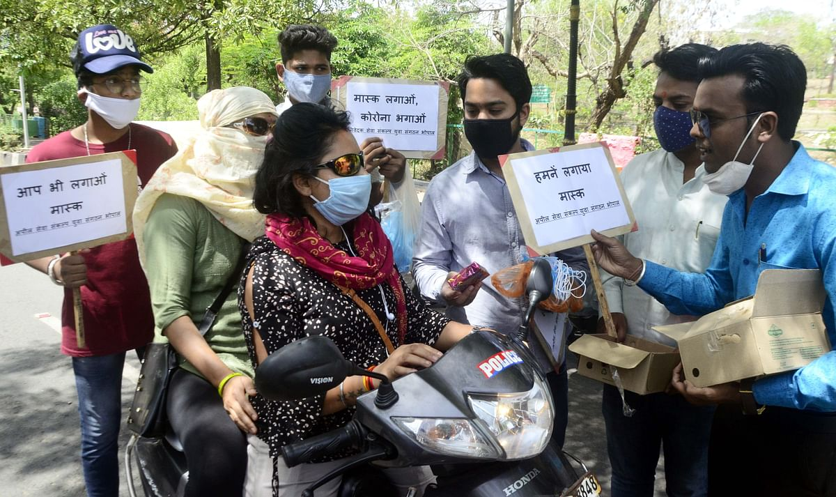 Youths distribute prizes at Vyapam Square in Bhopal to those who put on masks on Friday.