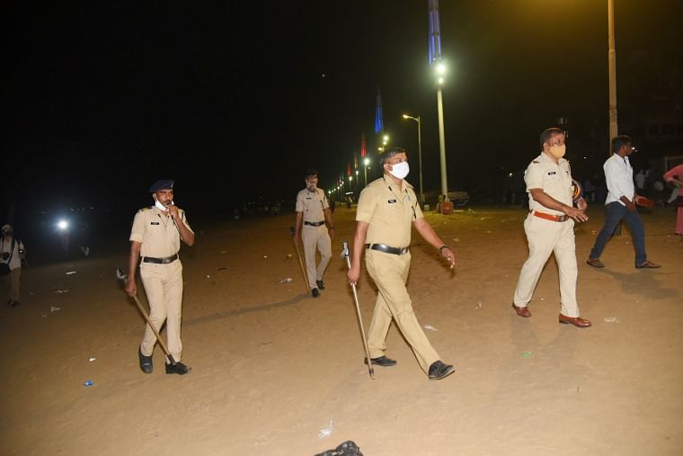 Police personnel conduct a flag march at Juhu Beach during night curfew, imposed by the authorities to curb the spread of coronavirus, in Mumba
