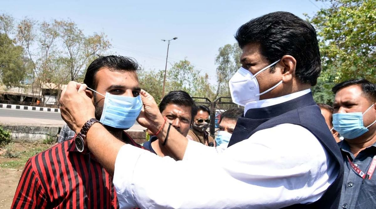 Pic 7: Revenue and transport minister Govind Singh Rajput distributes masks among commuters at the ISBT Square in Bhopal on Wednesday.