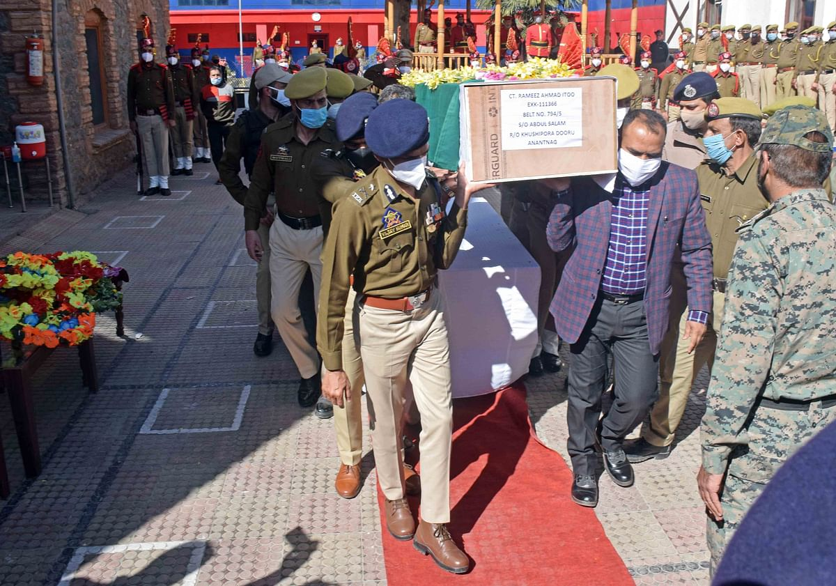 Senior police officers carry a coffin containing the body of the slain policeman during the wreath-laying ceremony at the police headquarters in Srinagar.