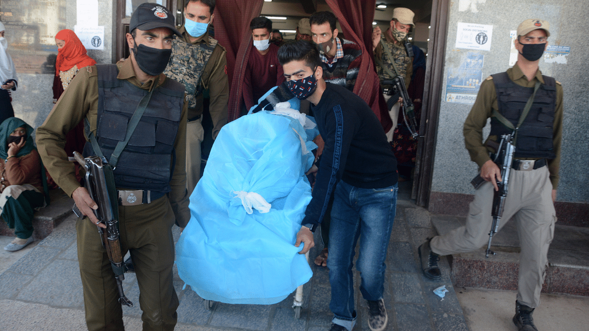 People carrying the succumbed police cop on a stretcher at a hospital in Srinagar, Kashmir.