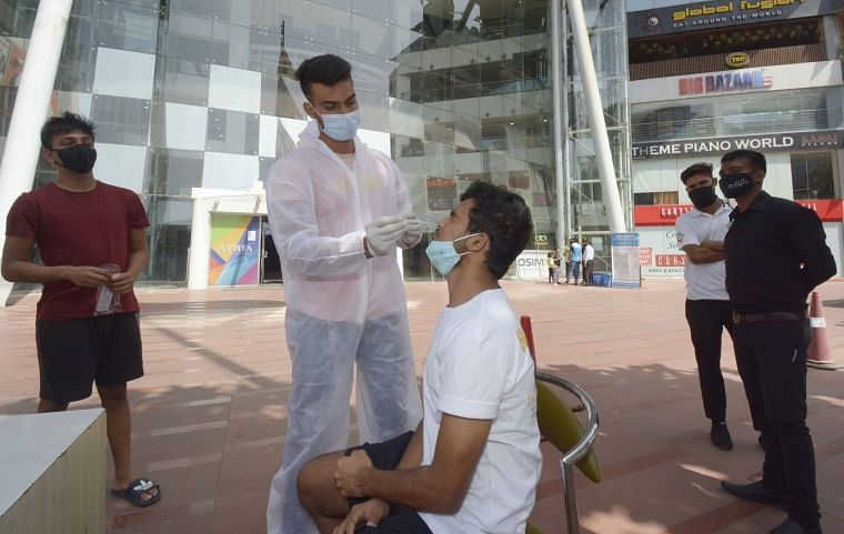 A healthcare worker conducts antigen tests at a mall in Worli on Saturday