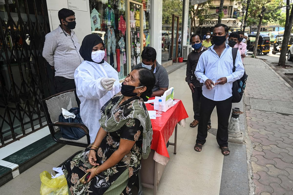 A health worker takes a swab sample for a Rapid Antigen Testing (RAT) at a roadside market following restrictions imposed by the state government amidst rising Covid-19 coronavirus cases, in Mumbai on April 6, 2021.