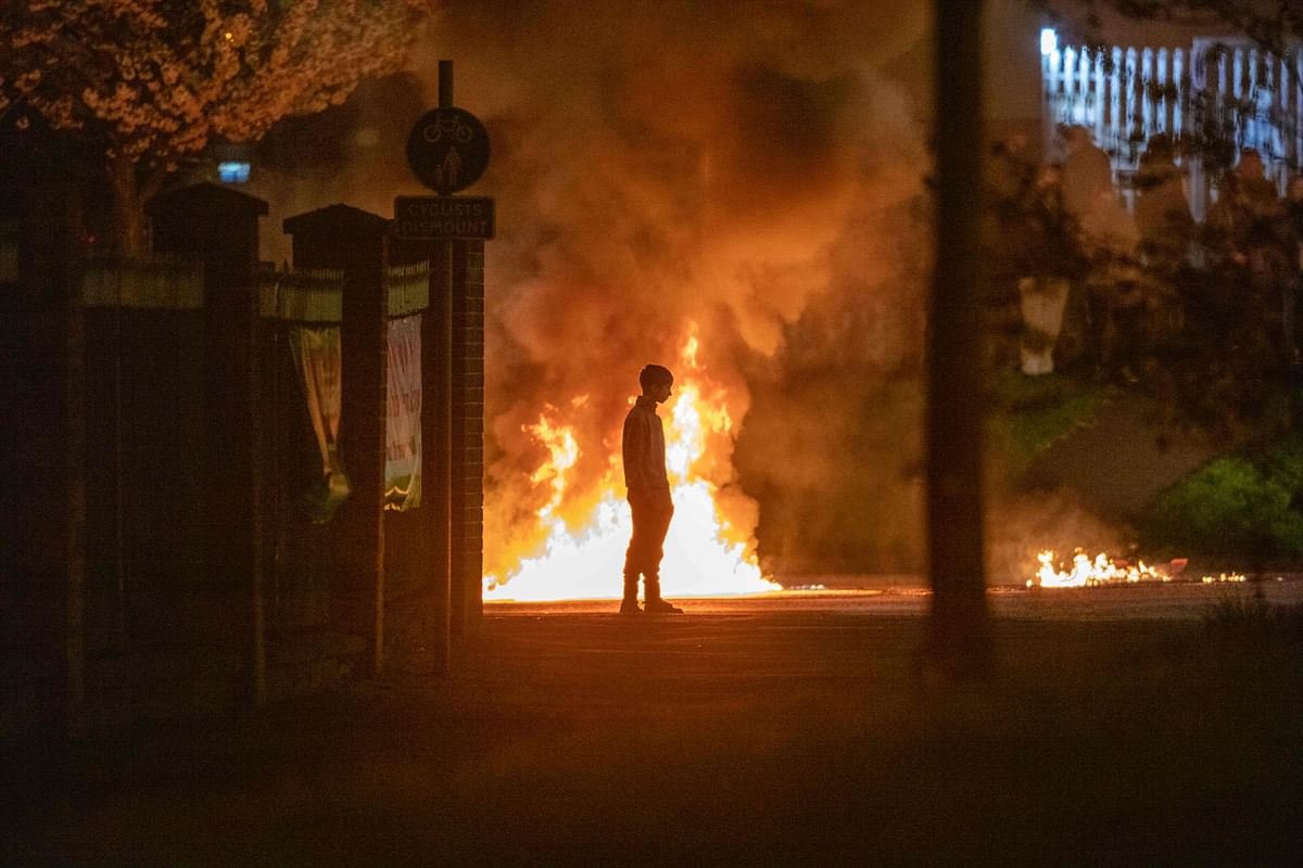 A boy stands and looks on as flames and smoke rises behind him at the scene of violence in Newtownabbey, north of Belfast, in Northern Ireland on April 3, 2021.