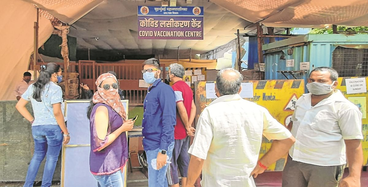 People wait at a Covid-19 vaccination centre at Dahisar east, in Mumbai, on Sunday.